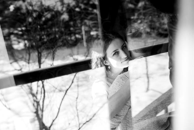 Ragazzo e donna in casa vicino alla finestra che si affaccia su un paesaggio innevato