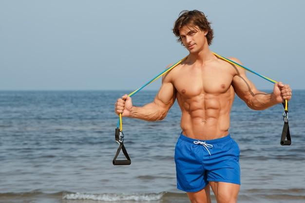 Ragazzo che lavora con elastico sulla spiaggia