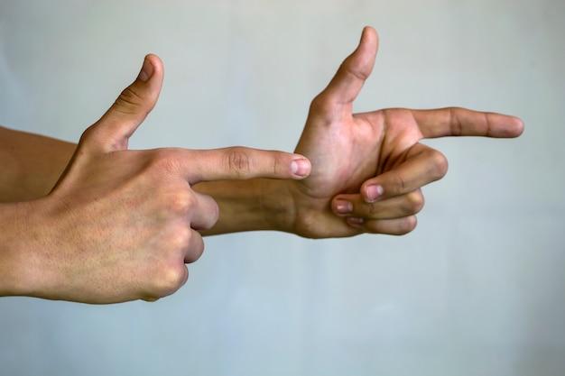 Le dita dei ragazzi mostrano il primo piano delle pistole su uno sfondo bianco