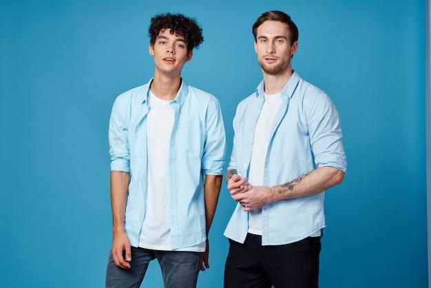 Ragazzi con magliette identiche e una maglietta su uno sfondo blu, gli amici gesticolano con le mani