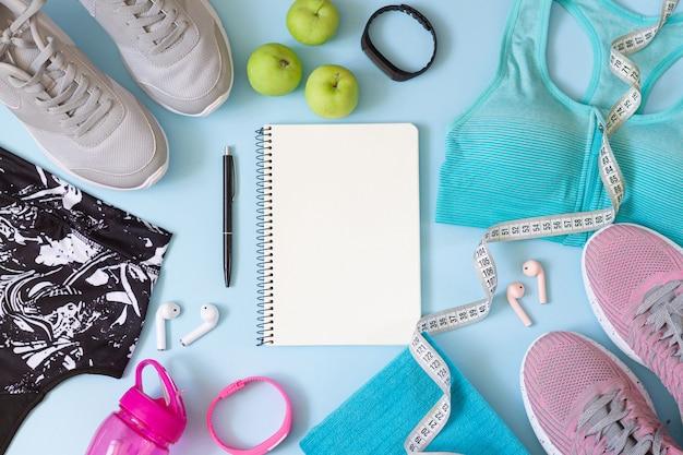 Abbigliamento da palestra e accessori per donne con quaderno bianco per piano di allenamento