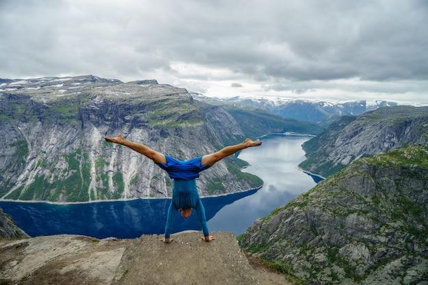Ginnasta in piedi con le mani sul bordo con fiordo sullo sfondo vicino a trolltunga. norvegia.
