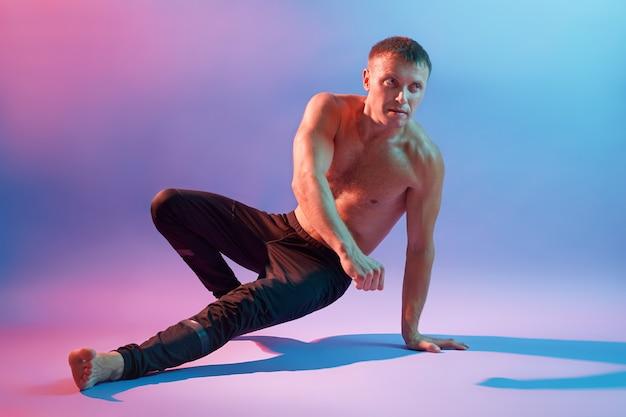Ginnasta che si allena per mantenere l'equilibrio del suo corpo mentre viene fotografato contro lo spazio al neon, veste pantaloni neri, guardando da parte, mostra le sue forme perfette.
