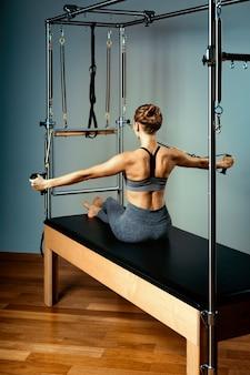 Pilates della donna della ginnasta che allungano lo sport nella ragazza dell'istruttore del letto del riformatore. sfondo blu, corpo sano, ginnastica allungante. concetto di forma fisica.