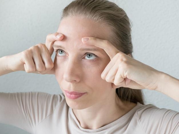 Ginnastica per il viso. la donna fa esercizi ringiovanenti per il viso
