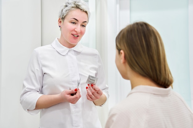 Medico del ginecologo che consulta paziente che mostra preservativo per la contraccezione