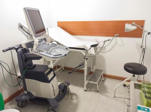 Sala ginecologica con macchina ad ultrasuoni e barella.