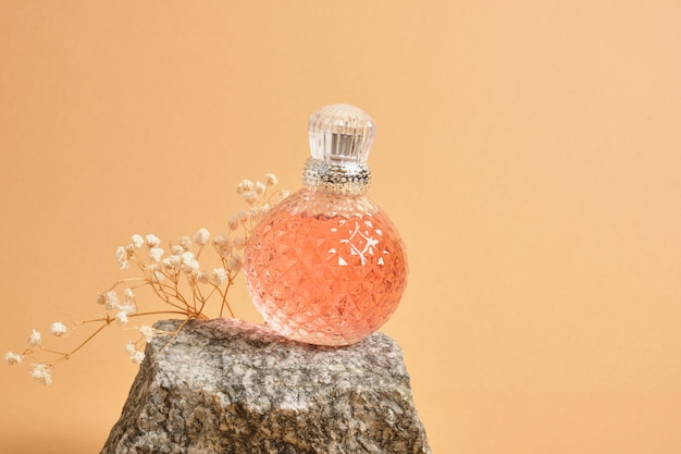 Fiore di gypsophila, rosa di cristallo sferico mock up bottiglia di profumo in bianco con tappo d'argento su pietra naturale su sfondo beige