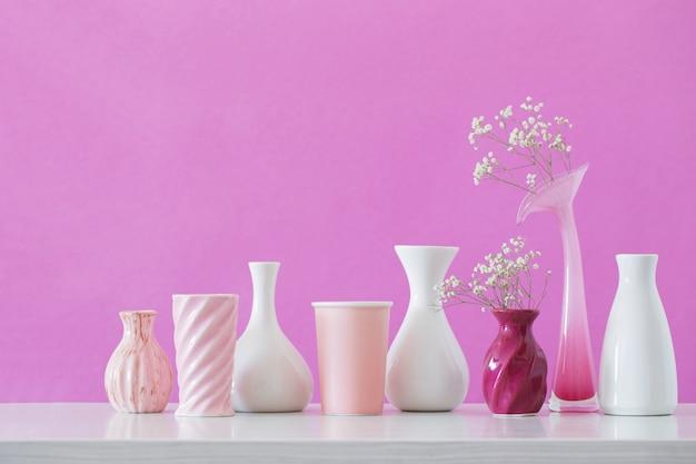 Fiori di gypsophila in vasi su sfondo rosa