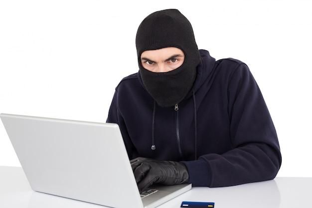 Pirata informatico in passamontagna che incide un computer portatile