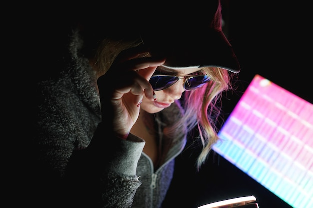 La ragazza hacker con un berretto e occhiali da sole davanti a un computer alla luce al neon tiene in mano lo smartphone