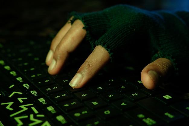 Mano di hacker che ruba i dati dal laptop dall'alto verso il basso