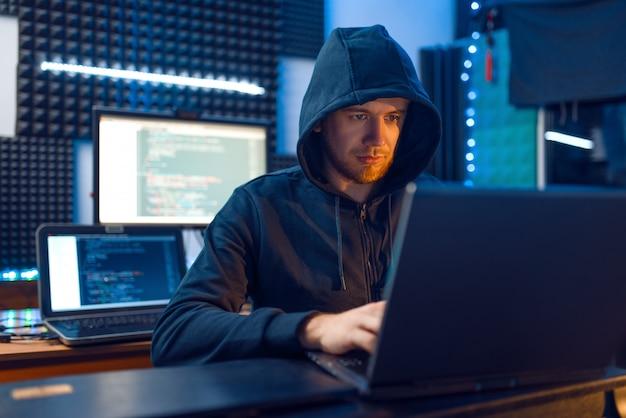 Hacker in cappa sul posto di lavoro con laptop e pc desktop, password o hacking di account, utente darknet.