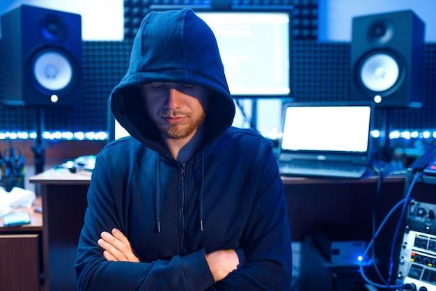 Hacker in cappa sul posto di lavoro con laptop e pc, password o hacking dell'account.