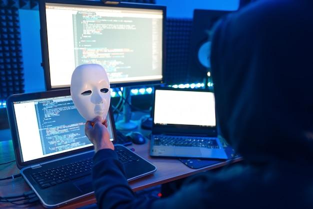 Hacker in hood tiene la maschera in mano e sul posto di lavoro con laptop e pc, password o hacking dell'account.