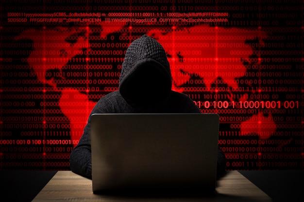 Hacker in una giacca con cappuccio con un laptop si siede al tavolo. aggiunte icone di furto d'identità, dirottamento dell'account, furto di dati bancari e mappa del mondo