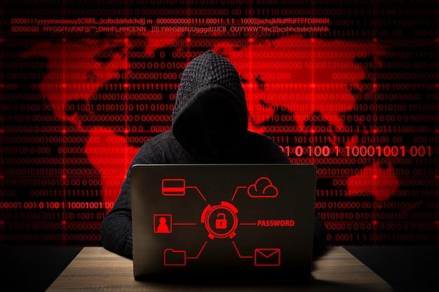 Hacker in una giacca con cappuccio con un laptop si siede al tavolo
