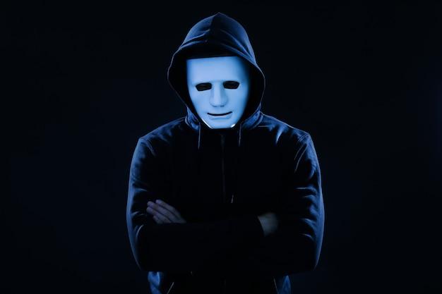 Hacker in maschera sulla superficie scura