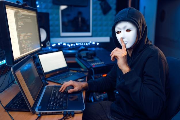 Hacker in maschera e cappuccio seduto al suo posto di lavoro con laptop e pc, rete o account di hacking.