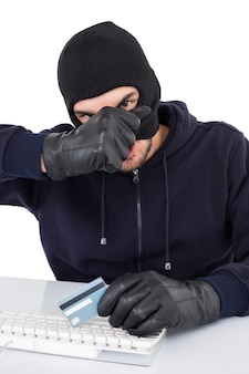 Hacker che rimuove il suo passamontagna per mostrare la sua faccia