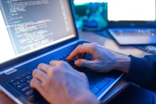 Hacker seduto al laptop, pirateria informatica