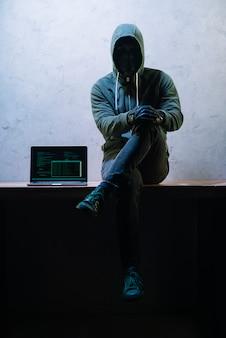 Hacker seduto accanto al computer portatile Foto Premium