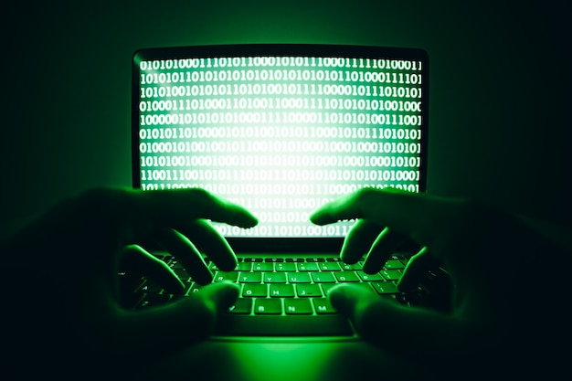 Hacker che utilizza laptop per codificare virus o malware per l'hacking del server internet attacco informatico