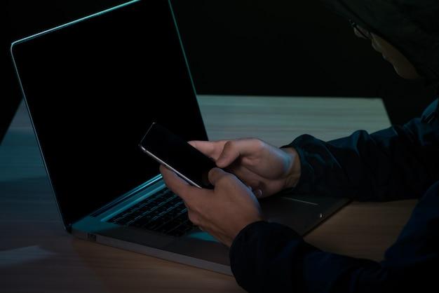 Hacker che utilizza uno smartphone. ambiente notturno molto buio
