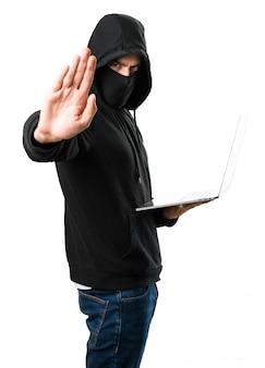 Pirata informatico con il suo computer che fa il fanale di arresto su fondo bianco isolato