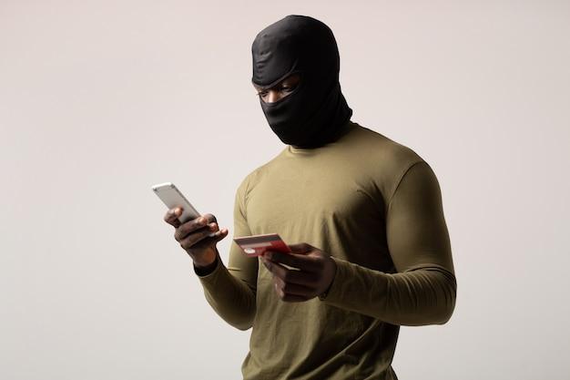 Hacker con cellulare e carta di credito in mano
