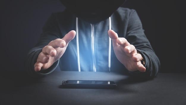 Hacker con smartphone. crimine informatico