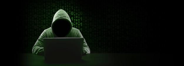 Hacker senza volto in una cappa su codice binario, mock-up panoramico con spazio per il testo