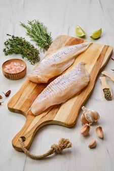 Filetto di eglefino con condimento su tagliere di legno