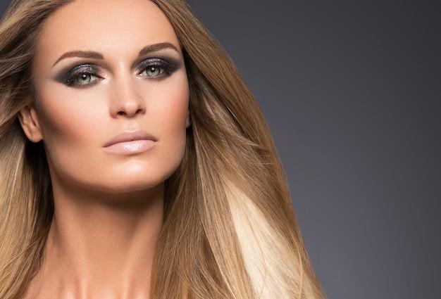 Capelli bella lunga acconciatura bionda donna moda trucco pelle sana e capelli sfondo nero. colpo dello studio.