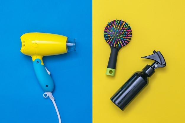Prodotti per la cura dei capelli sulla parete gialla e blu. dispositivi per asciugare i capelli su una parete colorata.