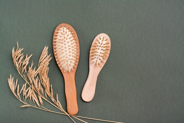 Cura dei capelli. due pettini di legno e spighe d'erba su uno sfondo verde. copia spazio