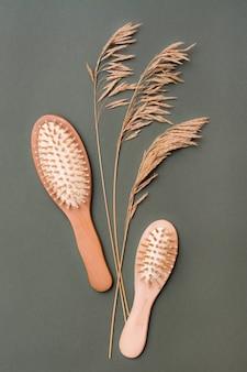Cura dei capelli. due pettini di legno e spighe d'erba su uno sfondo verde. vista verticale