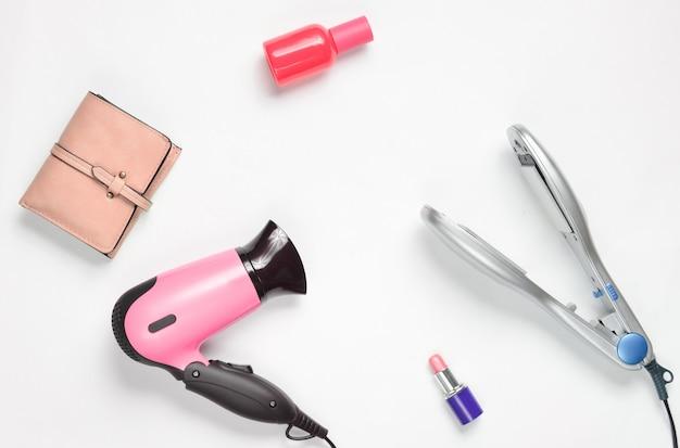 Asciugacapelli, ferro da stiro, rossetto, bottiglia di profumo, borsa isolata su superficie bianca
