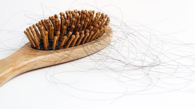 Perdita di capelli nel pettine caduta dei capelli problema serio quotidiano su sfondo bianco