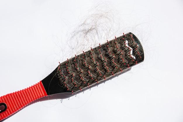Problema di caduta dei capelli. pettine rosso e nero su sfondo bianco.