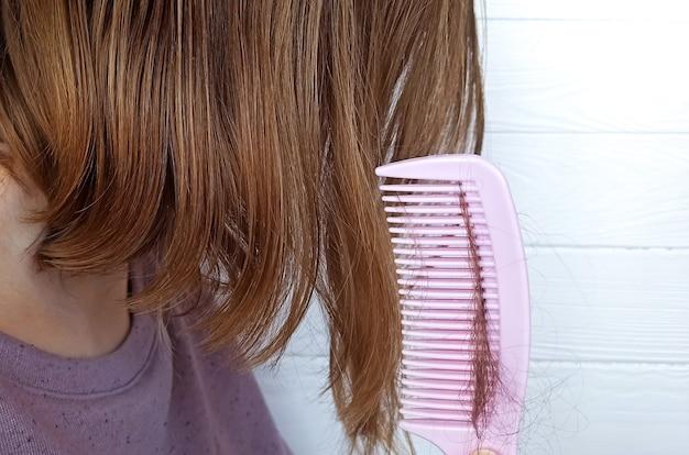 Problema di caduta dei capelli. la donna sta tenendo con il pettine rosa.