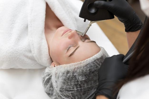Procedura di cosmetologia di rimozione dei capelli da un terapista presso la clinica spa di bellezza cosmetica. epilazione laser e cosmetologia