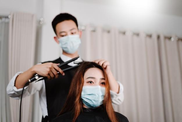 Concetto di parrucchiere sia parrucchiere maschile che cliente femminile che indossa una maschera protettiva per il viso durante il processo di taglio dei capelli.