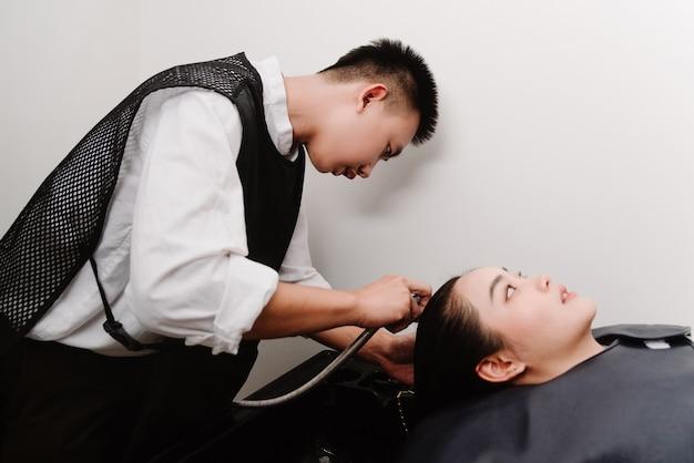 Concetto di parrucchiere un parrucchiere maschio che tiene una doccia d'acqua lavando delicatamente i capelli di una cliente femminile.