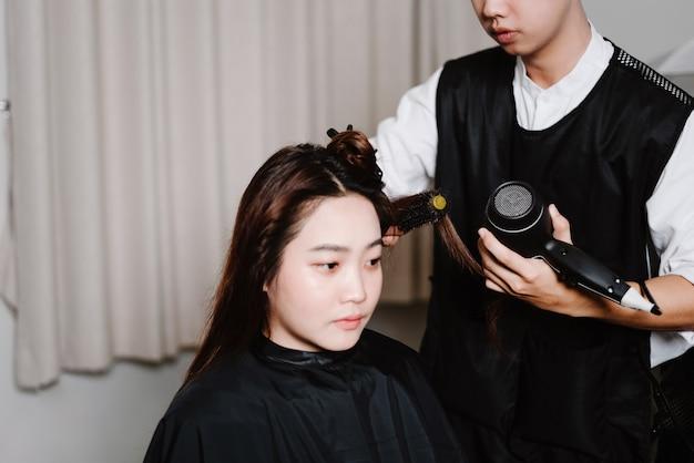 Concetto di parrucchiere un parrucchiere maschio che utilizza un asciugacapelli che asciuga i capelli bagnati di una cliente femminile dopo il processo di lavaggio dei capelli.