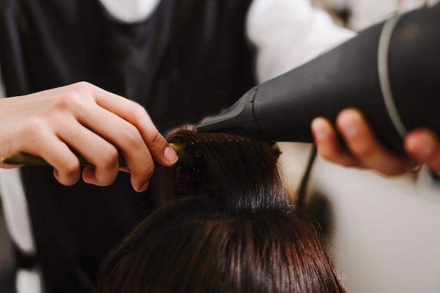 Concetto di parrucchiere un parrucchiere maschio che usa un pettine per afferrare una ciocca di capelli e usa un asciugacapelli per asciugare e stirare