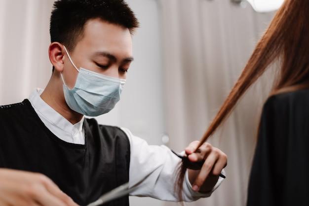 Concetto di parrucchiere un parrucchiere maschio che lavora con le forbici che tagliano e acconciano i capelli di una cliente femminile.