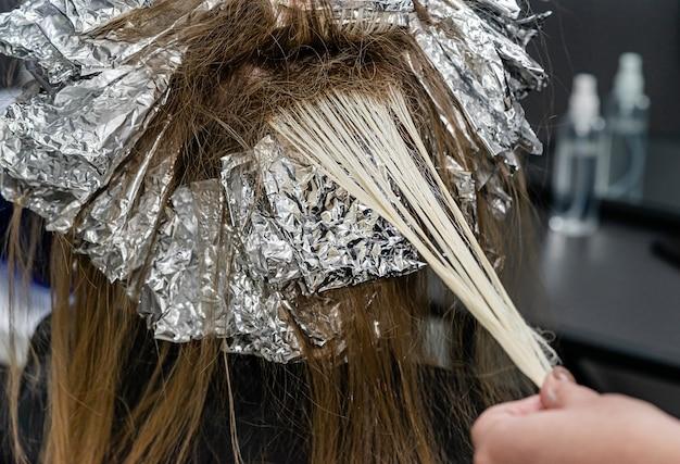 Parrucchiere che controlla i capelli dei modelli durante il processo di sbiancamento. schiaritura dei capelli alla moda con la tecnica shatush.