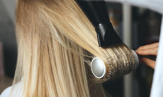 Parrucchiere che asciuga i capelli del cliente con una spazzola pettine e un asciugacapelli