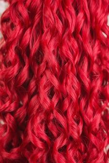 Primo piano di struttura dei capelli. ragazza rossa con brillante parrucca ondulata brillante. bellezza naturale. ragazza con taglio di capelli perfetto. capelli crespi rossi voluminosi. colorare in salone. acconciatura brillante. parrucca lunga
